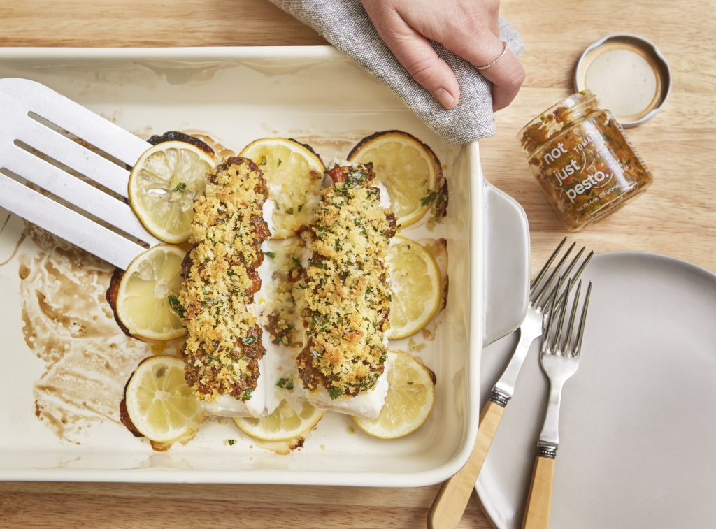 baked fish with lemony breadbrumbs and not just pesto being taken out of pan